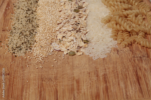 Multiple organic grains, including fusilli pasta, jasmine rice, quinoa, hemp seed, and a mix of grains and seeds oatmeal, on a cutting board on a rustic farm picnic table in summer.