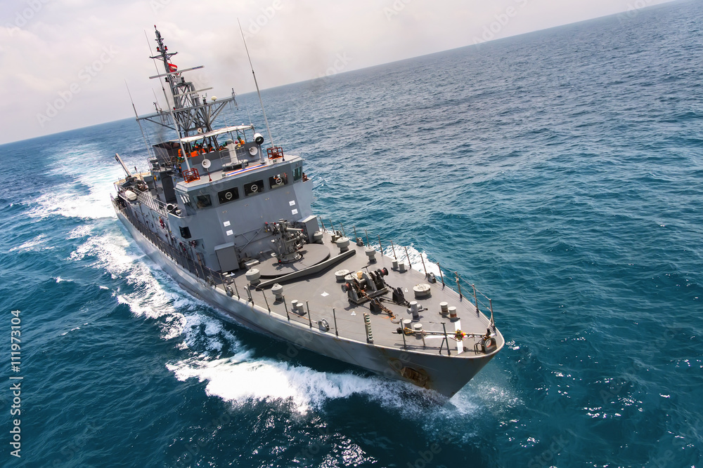 Fototapeta Military navy ships in a sea bay with fishing boat,view from aerial