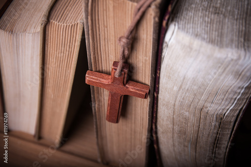 Fotografie, Obraz  Closeup of wooden Christian cross necklace next to holy Bible