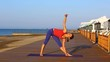 Pretty woman doing yoga on the beach. Sporty woman sitting in yoga position at sea view background.
