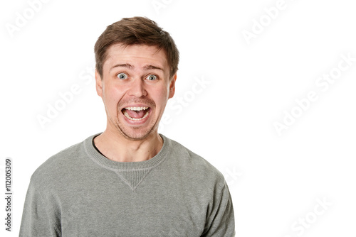 Fényképezés Happy young man with manic expression, on gray background