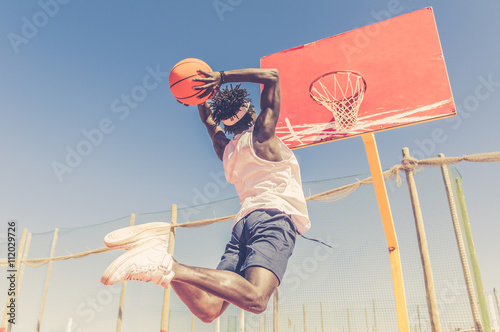 obraz lub plakat Basketball street player making a slam dunk outdoor