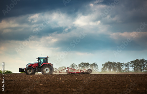 Farming tractor plowing and spraying on field плакат