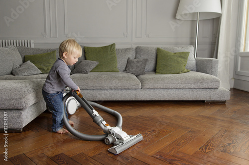 Toddler Vacuuming A Wooden Floor In The Living Room Buy This Stock
