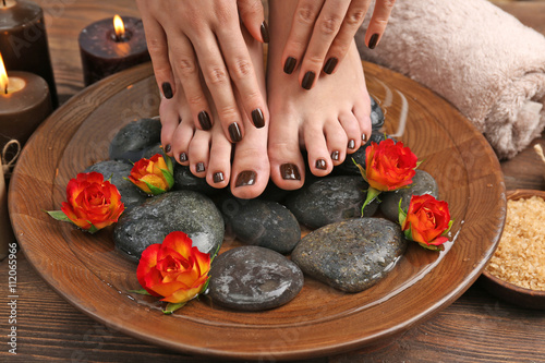 Foto op Plexiglas Spa Manicured female feet and hands in spa wooden bowl with flowers and water closeup
