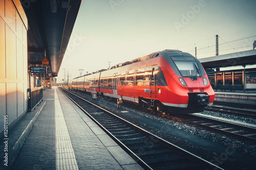 plakat Beautiful railway station with modern red commuter train at colorful sunset in Nuremberg, Germany. Railroad with vintage toning