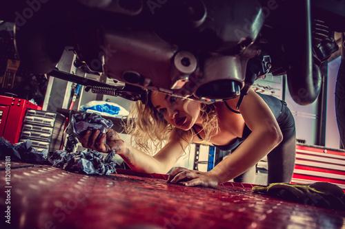 Blond woman repairing motorcycle.