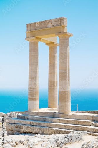 Plakat Słynny grecki świątynia trzy filary przeciw jasne błękitne niebo i morze w Lindos Akropol athena Ateny, Grecja