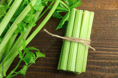 Fotografia  Fresh green celery wrapped with a rope on a brown wooden background