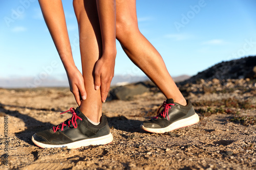 Runner woman with hurt ankles in pain during marathon Canvas Print