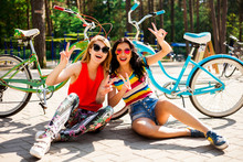 Two Beautiful Happy Funny Hipster Girl, Sitting On The Pavement, There Are A Number Of Blue And Green Bikes, Teenagers Laughing And Posing For The Camera, Best Friends, Colorful Casual Wear, Happy