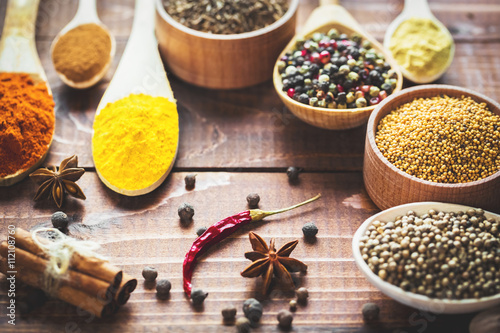 Fotografia  Beautiful colorful spices in wooden spoons and bowls on an old wooden brown table