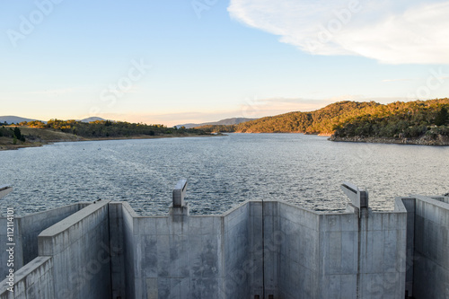 Photo sur Toile Barrage Weighted flood gates on Jindabyne Dam, Snowy River. The surrounding mountain landscape and cloudscape. Lake Jindabyne is part of the ground breaking 'Snowy Mountains Hydro-Electric Scheme'.