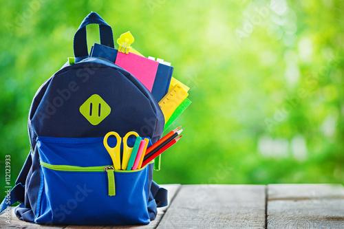 Fototapeta Full School backpack on wooden and nature background obraz