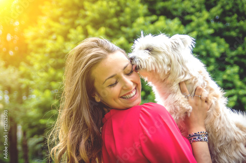 Fotografie, Obraz  Attractive caucasian girl having fun with her dog
