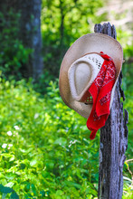 Cowboy Hat With Bandana Hanging On Fence Post