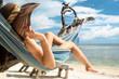 canvas print picture - Frau im Urlaub am Strand entspannt in Hängematte am Meer