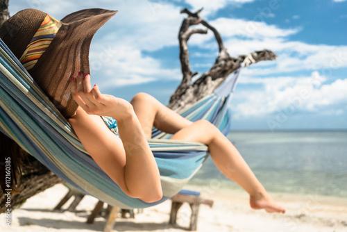 Fototapeta Frau im Urlaub am Strand entspannt in Hängematte am Meer obraz