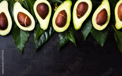 Fresh avocado with leaves on black background