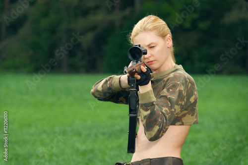 Foto op Canvas Jacht Pretty hunter girl aiming with hunting rifle in the outer wood.