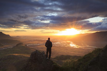 Silhouette Of A Man Standing On A Ledge Of A Mountain, Enjoying The Beautiful Sunset Over A  River Valley In Iceland.