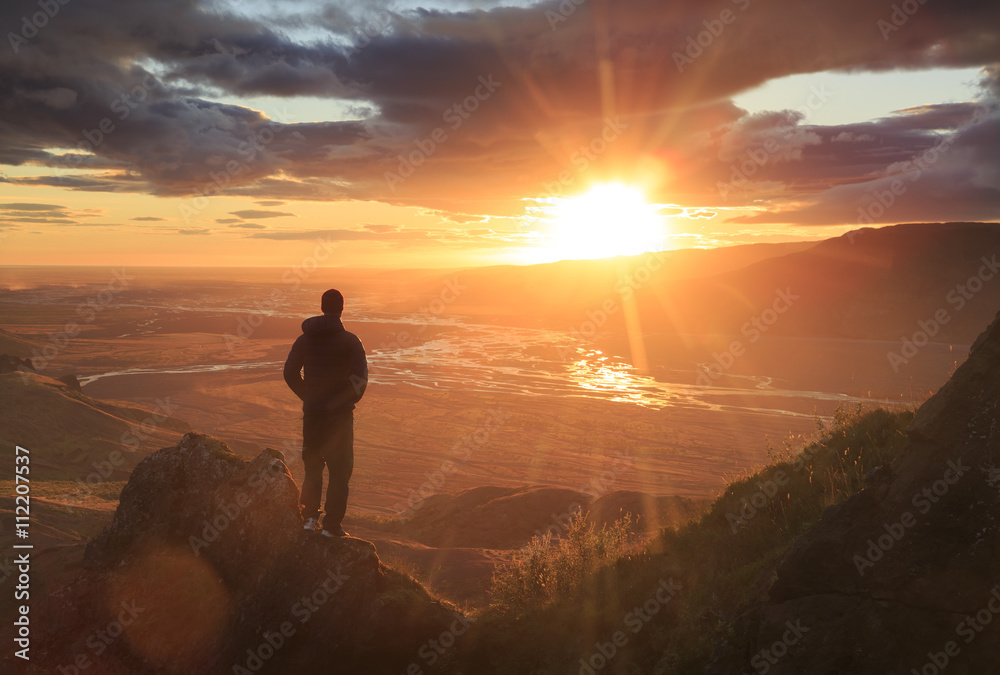 Fototapeta Man standing on a ledge of a mountain, enjoying the beautiful sunset over a wide river valley in Thorsmork, Iceland.