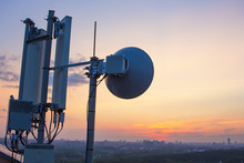 Base Station With Radio Relay Antenna On The Background Of A Sunset Over The City