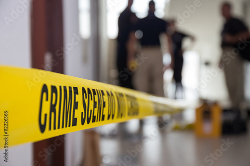 Foto crime scene tape in building with blurred forensic team backgrou