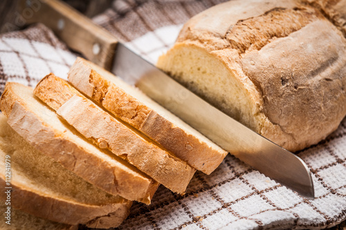 obraz dibond Sliced homemade bread on rustic wooden table
