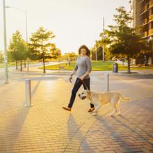 Caucasian Woman Walking Dog On Sidewalk