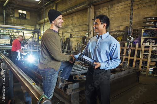 Worker and businessman shaking hands in factory Poster
