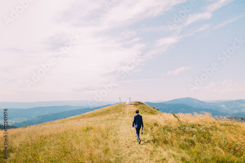 Fotografía  Stylish dressed man, holding a bottle of wine closing to hill with lone girl in