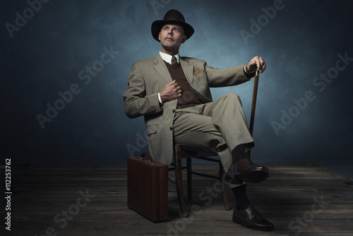 Fotografie, Obraz  Fashionable vintage 1940 business man with cane sitting on chair