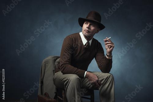 Fotografia  Stylish vintage 1940 business man smoking cigarette sitting on c