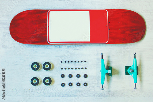 Photo  Red skateboard deck with other equipment on the white wood backgroung