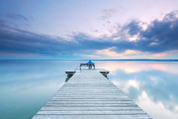 Panel Szklany Frau sitzt entspannt auf einer Bank am Steg am See