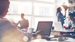 Startup team at work. Big open space office, laptops and paperwork. Business concept. Film effect and lens flare effect, blurry background