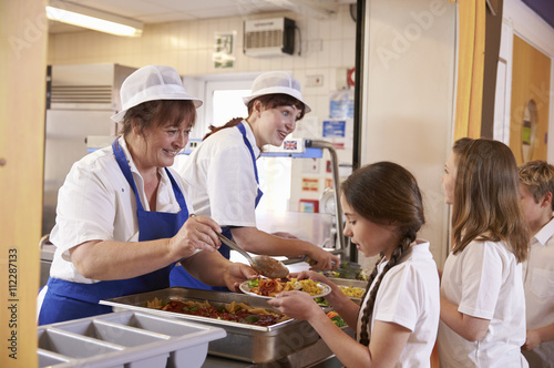 Foto Two women serving food to a girl in a school cafeteria queue