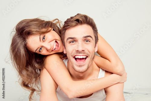 Fototapeta Cheerful smiling couple in love hugging in the bedroom obraz
