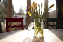Glass Vase Of Daffodils On Wooden Table