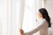 canvas print picture - close up of woman opening window curtains