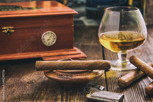 cigar and cognac with humidor in background Fototapeta