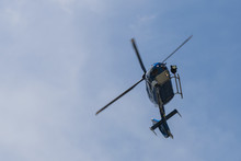 Police Helicopter On Blue Sky Flying And Searching Criminals.
