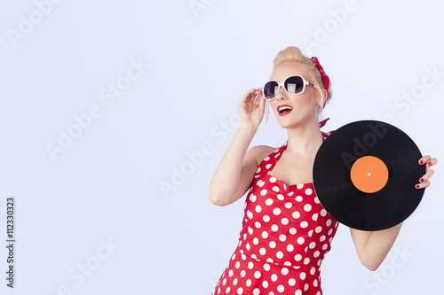 Valokuva  Pin-up girl in vintage dress holding a vinyl record