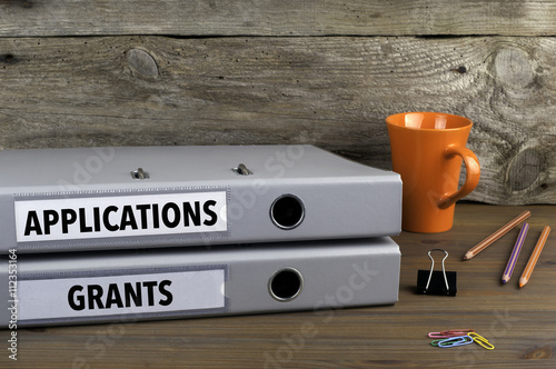 Fotografering  Applications and Grants - two folders on wooden office desk