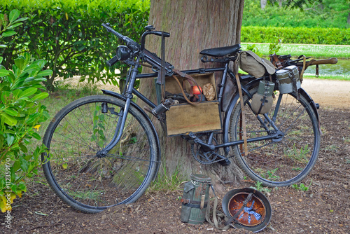 In de dag Fiets Vintage bicycle with World War 2 German Equipment Including Machine gun and Helmet.