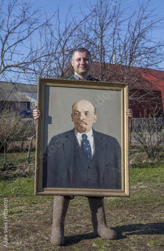 Villager with a portrait of Vladimir Lenin in his hands. Wallpaper Mural