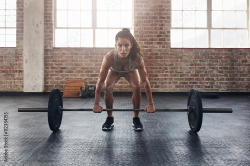 Foto op Plexiglas Fitness Female performing deadlift exercise with weight bar