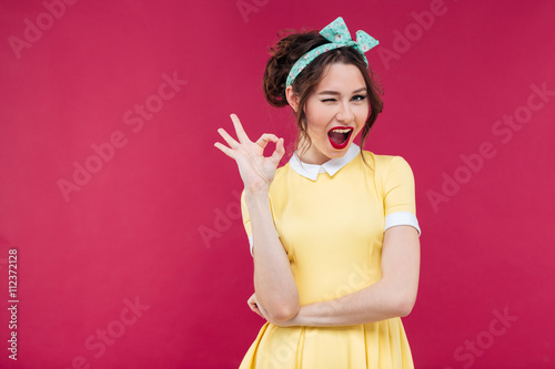 Photo  Happy attractive pinup girl in yellow dress showing ok sign
