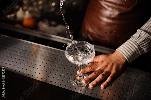Fotografia, Obraz Barman pouring into champagne glass and making a splash